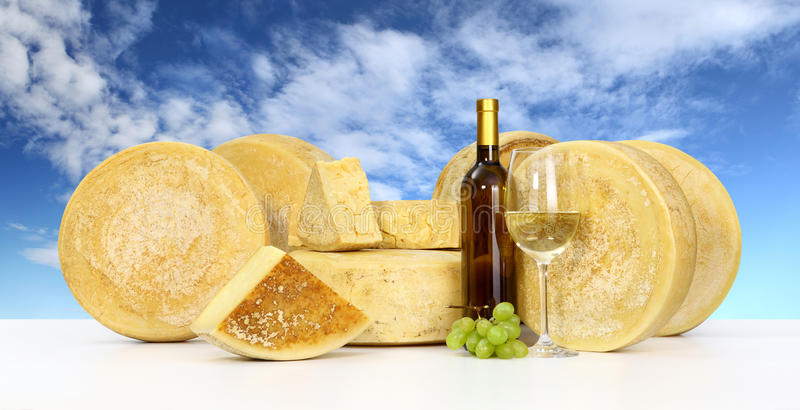Various forms of cheese wine glass bottle sky background royalty free stock photos