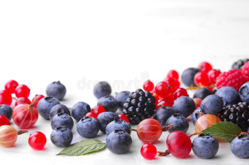 Various berries close-up including blueberries, raspberries, blackberries currants and gooseberries on a white wooden backgr stock image