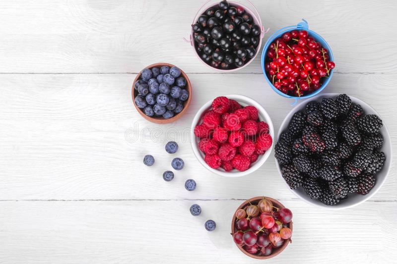 Various fresh berries close-up including blueberries, raspberries, blackberries and currants on a white wooden background. royalty free stock photo
