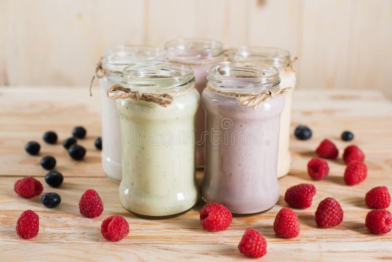 Various fresh berry milkshakes in glass jars stock images