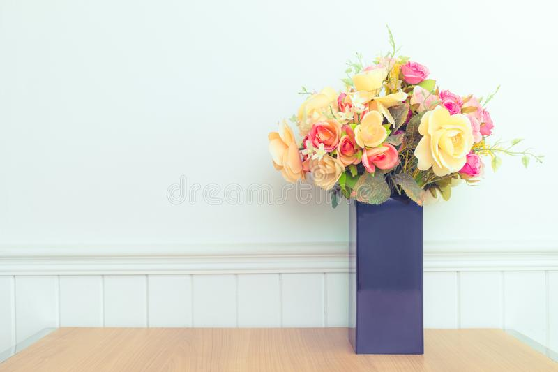 Various fresh flowers arrangement in vase on wooden table stock photography