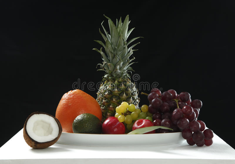 Various fresh fruits from coconut, pineapple, ripe, apples and grape on the white table in black background for healthy stock images