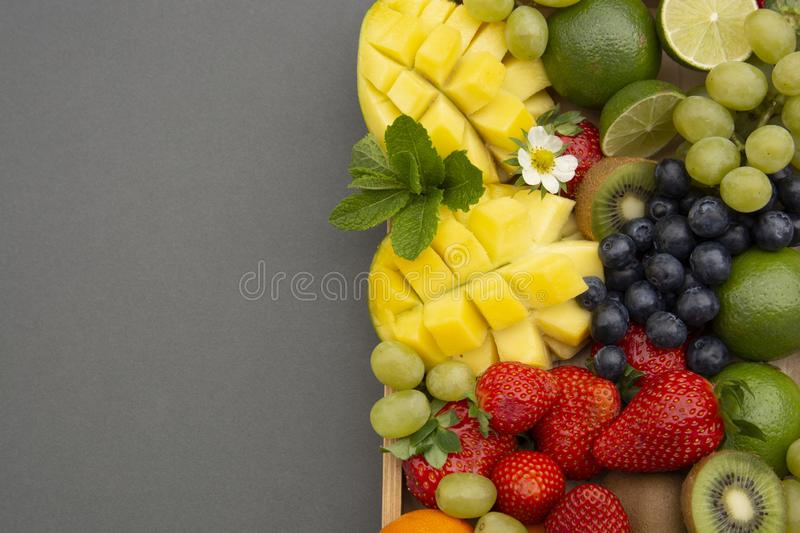 Various fresh fruits - mango, grapes, tangerine, lime, strawberry, kiwi, mint, on wooden tray and a gray background. Copy space stock photo