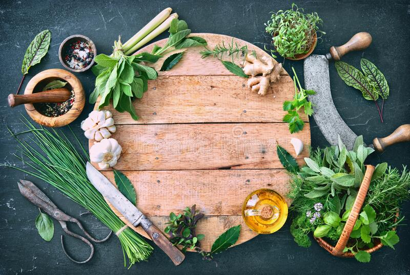 Various fresh herbs from garden with kitchen utensils on rustic table royalty free stock photo