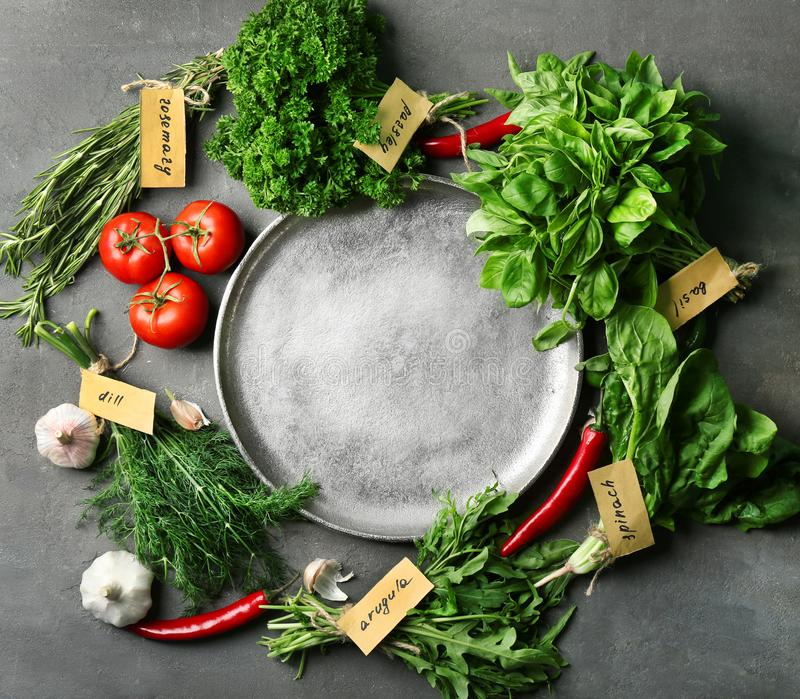 Various fresh herbs and vegetables with plate stock image