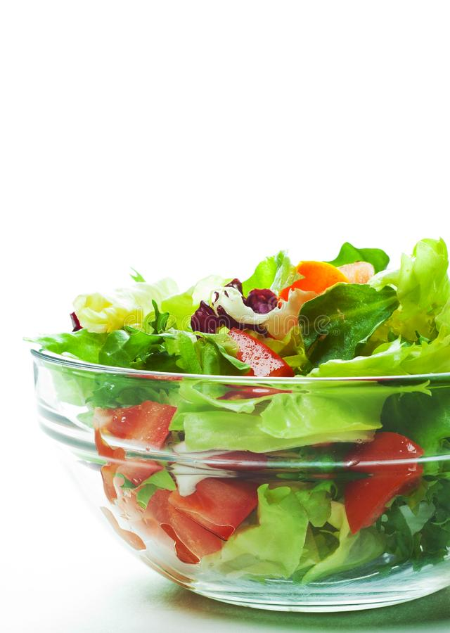 Various fresh mix salad leaves with tomato in glass bowl isolated on white royalty free stock image