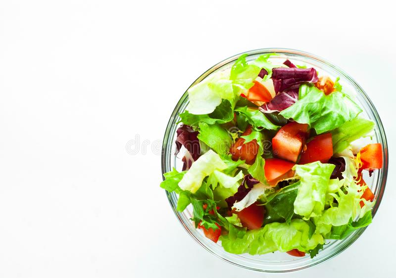 Various fresh mix salad leaves with tomato in glass bowl isolated on white royalty free stock photos