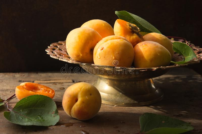 Various Fresh ripe apricots on wooden surface leaves fruits apricots on board cut apricots in half. Light blue rustic wood backgro stock image