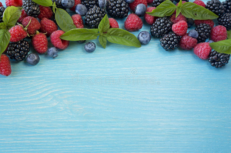 Various fresh summer berries on wooden background. Ripe blueberry, raspberry and blackberry with basil leaves royalty free stock photos