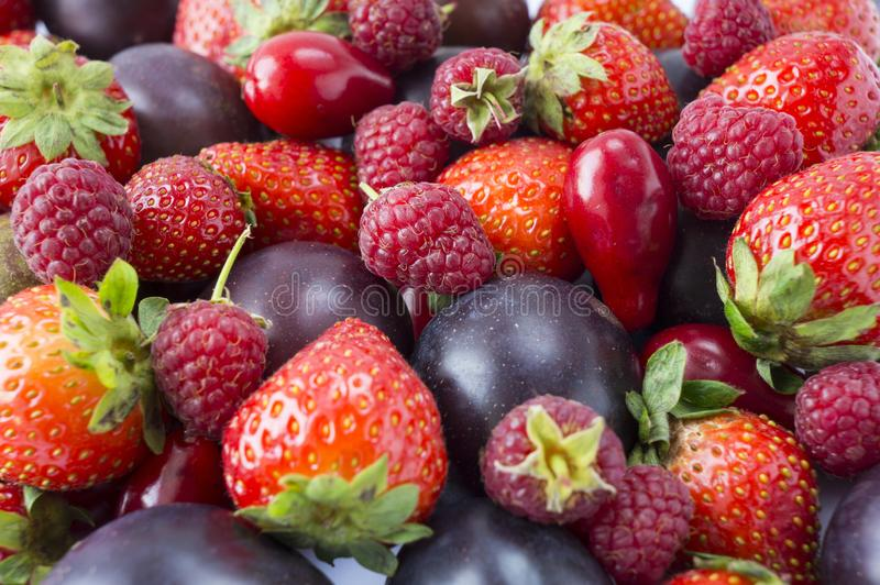 Various fresh summer fruits. Ripe strawberries, raspberries, red berries and plums. stock photography