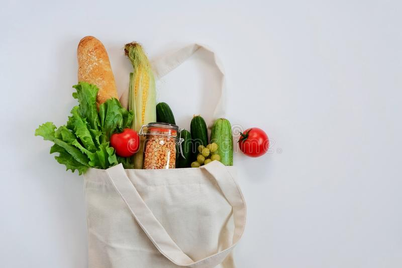 Various fresh vegetables and fruits, bread, cereals in an eco reusable bag. royalty free stock images