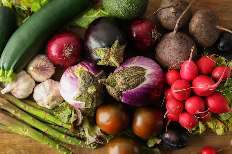 Various fresh vegetables with plums on wooden table stock image