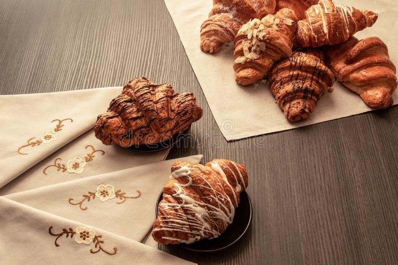 Baked croissants with almonds, chocolate and powdered sugar on a table with napkins and tablecloth, closeup. Various freshly baked croissants with almonds stock photos