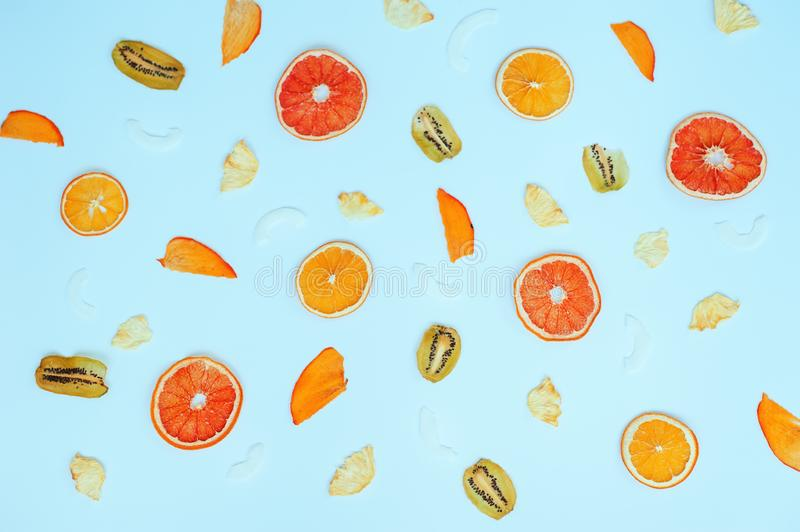 Various fruit chips on blue background. Assorted dehydrated apple, banana, kiwi, orange fruit chips - healthy vegan snack. Health. Sport concepts stock images