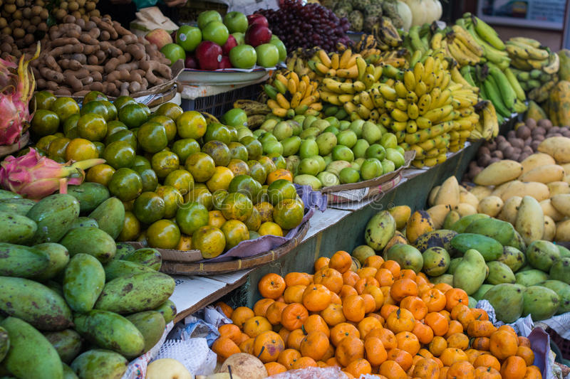 Various fruits on a shelf in Asian food market. Display of Various fruits on a shelf in Asian food local market. Fruit market with various colorful fresh fruits royalty free stock photos