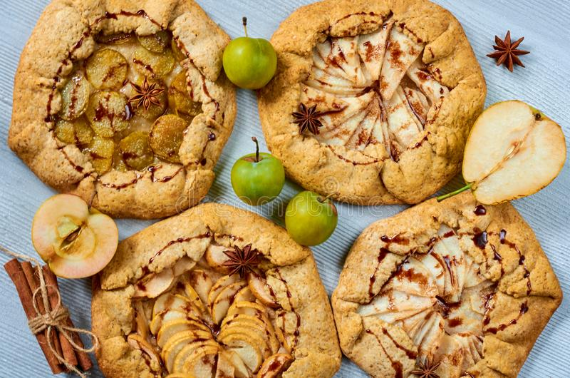 Various fruits tarts with chocolate topping on the gray concrete background. Vegetarian healthy autumn dessert - galette. With fresh apples, plums and pears stock photography