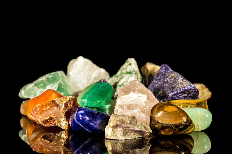 Various gemstones, uncut and Tumble finishing. With black background and reflection royalty free stock photos