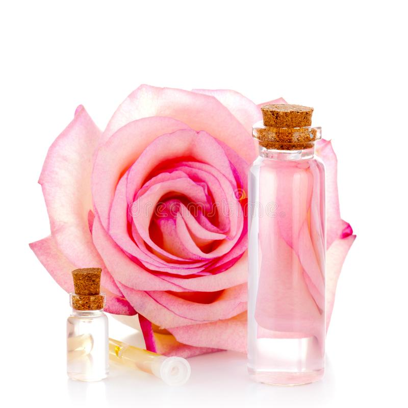 Various glass bottles with transparent liquid and pink rose stock image