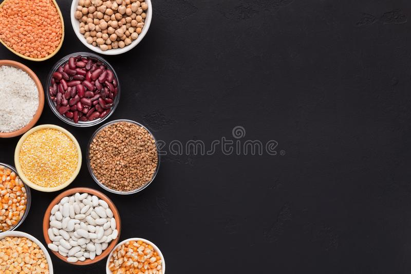 Various grains in different bowls on black background royalty free stock image