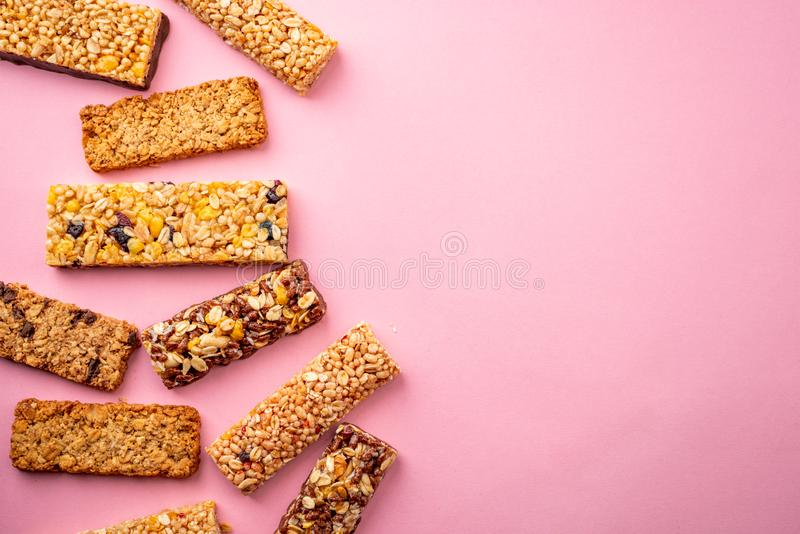 Various granola bars on pink background with copy space royalty free stock photo