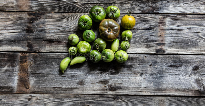 Various green tomatoes on simple wooden background for organic menu royalty free stock images