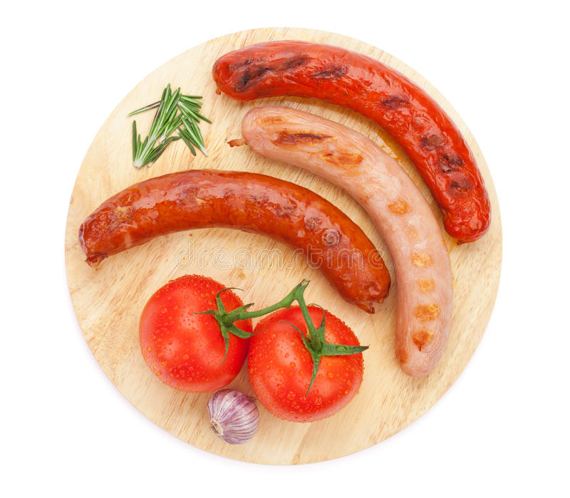 Various grilled sausages with condiments and tomatoes royalty free stock photography