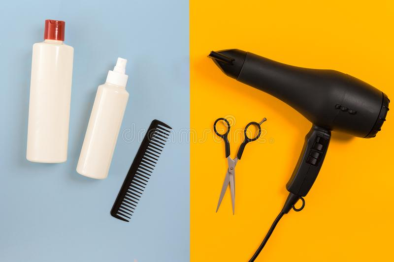 Various hair styling devices on the color blue, yellow paper background, top view. Copy space. Still life. Mock-up. Flat lay stock image