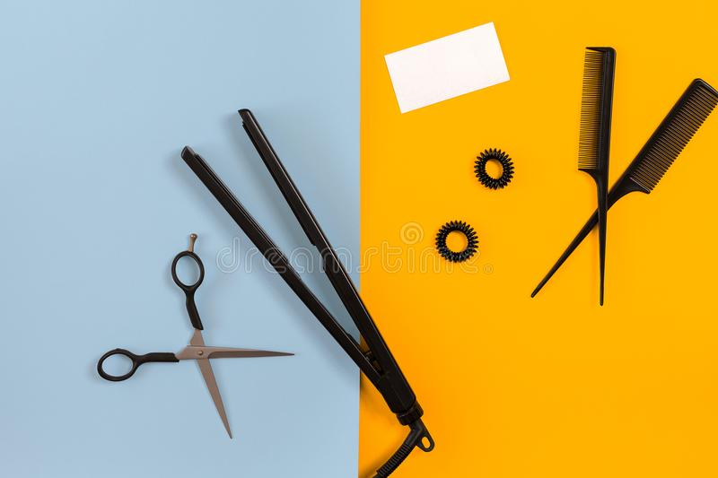 Various hair styling devices on the color blue, yellow paper background, top view. Copy space. Still life. Mock-up. Flat lay royalty free stock image