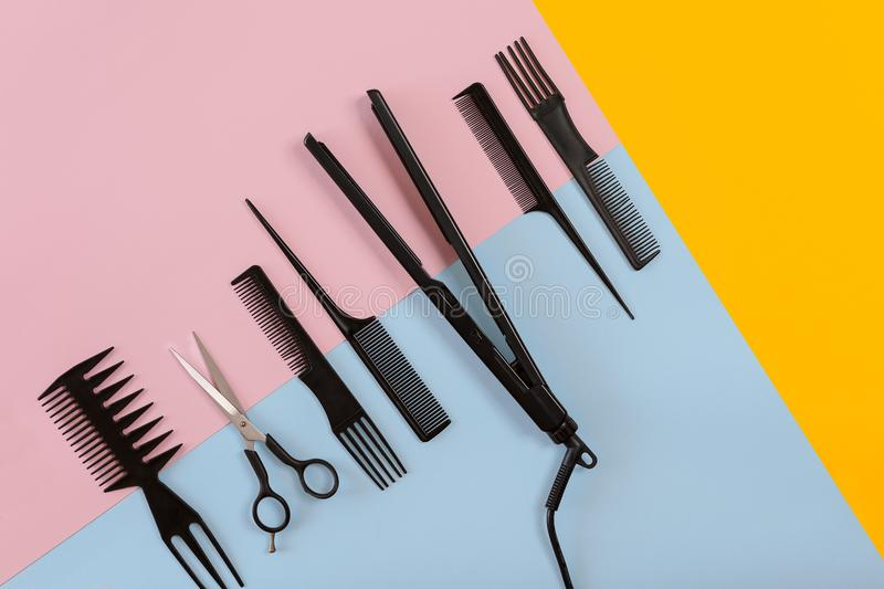 Various hair styling devices on the color blue, yellow, pink paper background, top view. Copy space. Still life. Mock-up. Flat lay royalty free stock photography