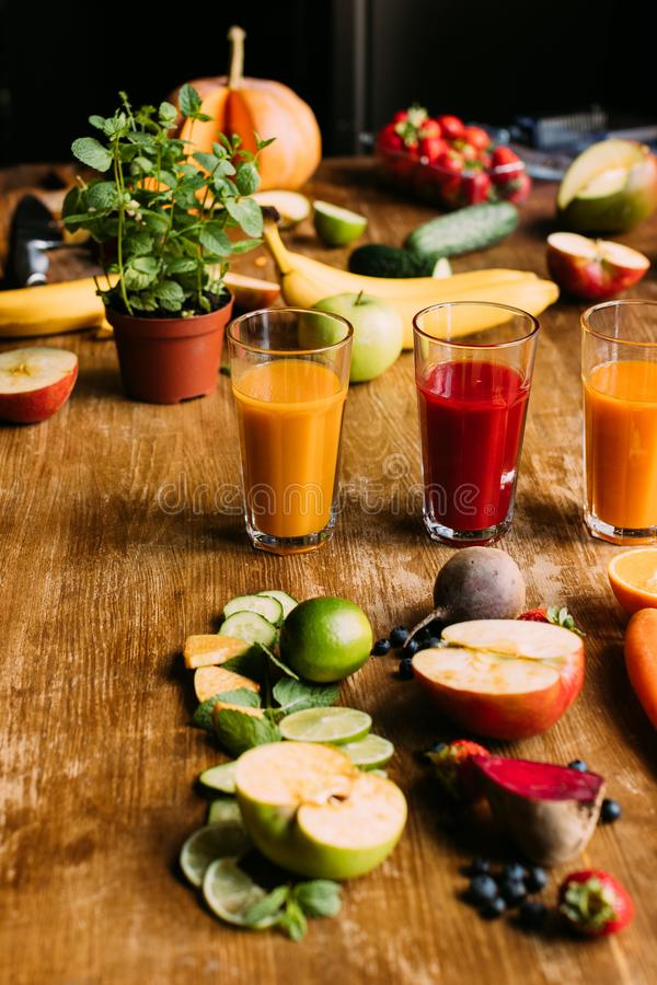 Various healthy smoothies in glasses and fresh ingredients. On wooden table royalty free stock photo
