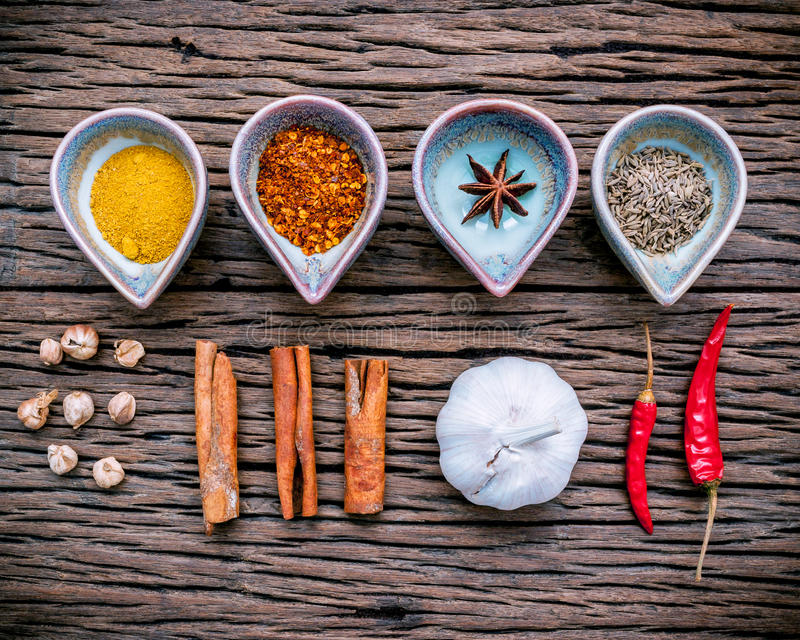 Various herbs and spices in ceramic bowl . Food and cuisine ingredients on rustic wooden background. royalty free stock image