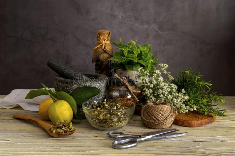 Various herbs and spices, lemons and olive oil on a wooden table. Various useful herbs and spices. Mint, origano, rosemary, lemons, olive oil in a bottle stock photos