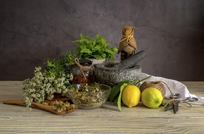 Various herbs and spices, lemons and olive oil on a wooden table. Various useful herbs and spices. Mint, origano, rosemary, lemons, olive oil in a bottle stock photography