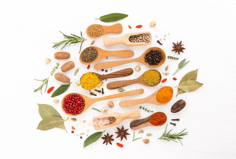 Various herbs and spices on wooden spoons. royalty free stock photography