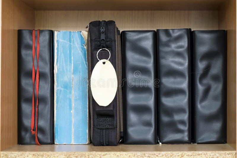 Various Holy Bible in the row in the ply wood book shelf royalty free stock photography