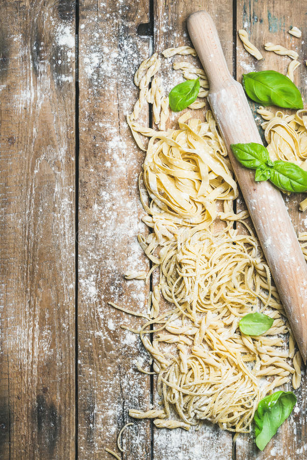 Various homemade fresh uncooked Italian pasta with flour, basil stock photography
