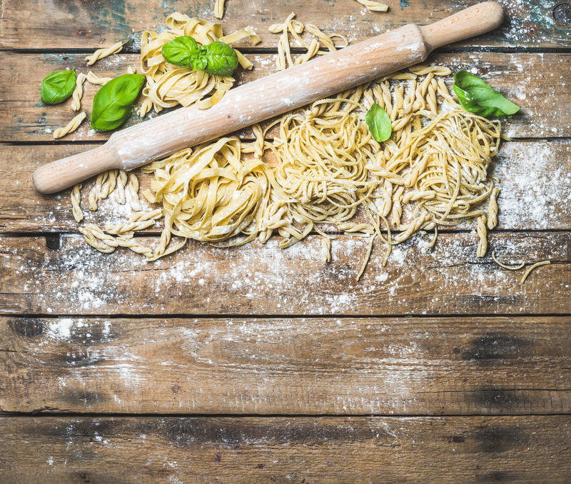 Various homemade fresh uncooked Italian pasta and plunger. Various homemade fresh uncooked Italian pasta with flour, green basil leaves and plunger on shabby royalty free stock photography