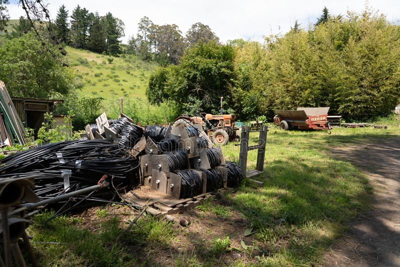 Various hoses, tractors and agriculture equipment scattered on grass at farm stock images