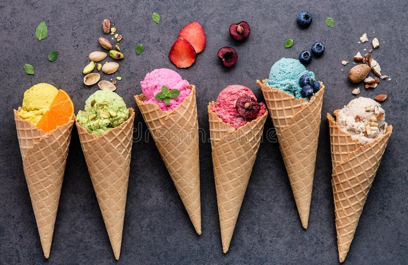 Various of ice cream flavor in cones blueberry ,strawberry ,pistachio ,almond ,orange and cherry setup on dark stone background . royalty free stock photos