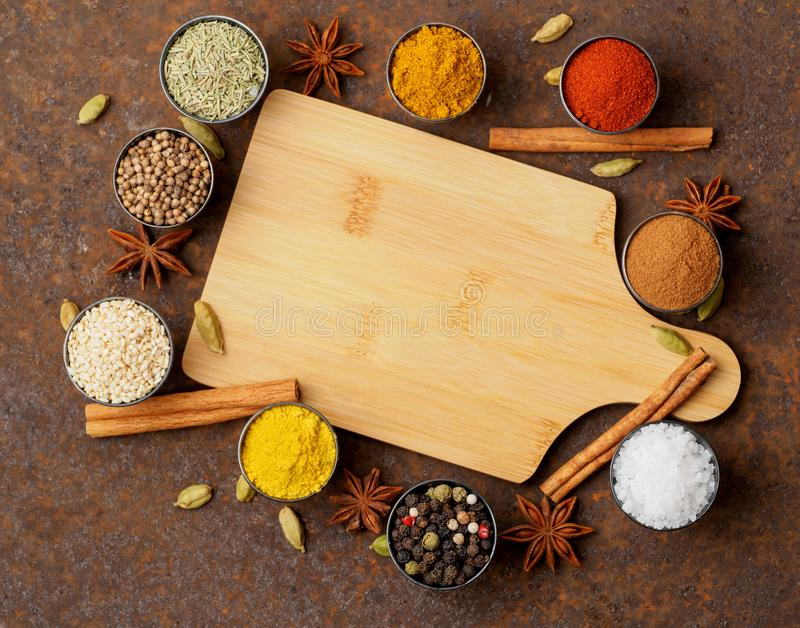 Various Indian spices in metal cups. Empty wooden Board, top vie stock photo