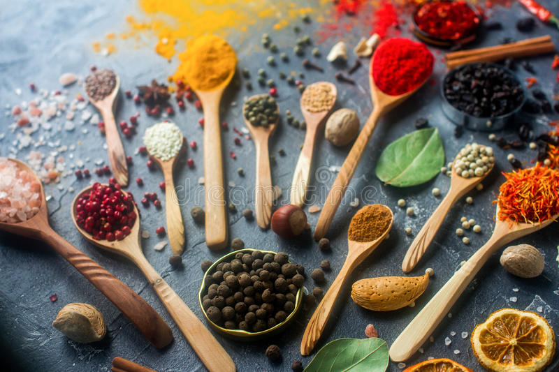 Various indian spices in wooden and silver spoons and metal bowls, seeds, herbs and nuts on dark stone table. Colorful spices royalty free stock images