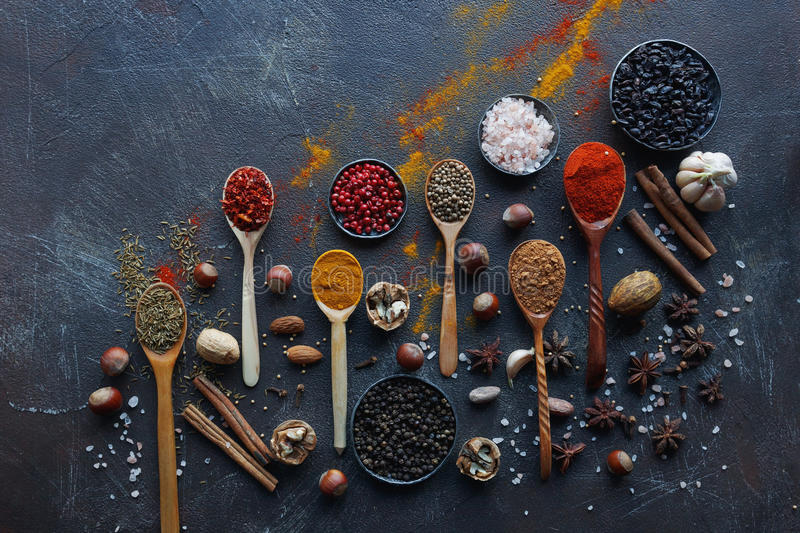 Various indian spices in wooden spoons and metal bowls and nuts on dark stone table. Colorful spices, top view. stock image