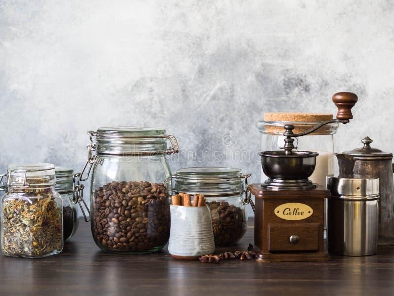 Various ingredients for making hot drinks - coffee, herbal tea, black tea. Glass jars with coffee beans, tea, sugar, coffee grinde royalty free stock images
