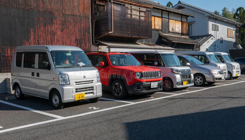 Various Kei cars park in reverse in Arashiyama, Japan. Kei cars will have yellow plate royalty free stock photo