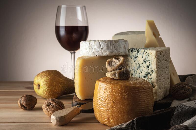 Various kind of cheese with glass of wine on wooden table. Cheese background stock images