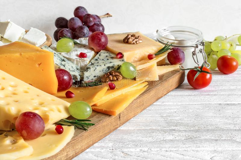 Various kind of cheese served on wooden cutting board with grapes, pomegranate, rosemary and tomatoes cherry royalty free stock photography