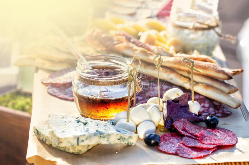 Various kind of cheese served on wooden table, traditional pieces of french and italy hand-made cheese. sunny day. Copyspace for royalty free stock images