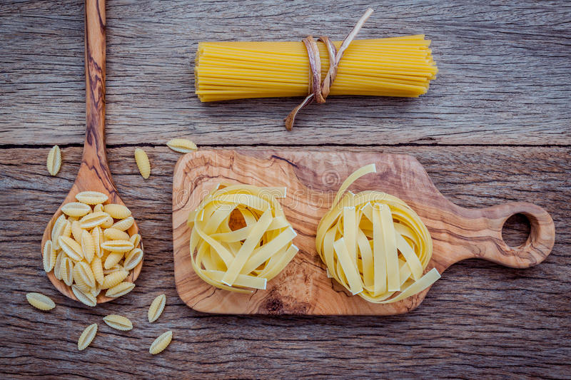 Various kind of Pasta Fettucini ,Spaghetti and Orecchiette Pugliesi on cutting board setup on shabby wooden background . royalty free stock images