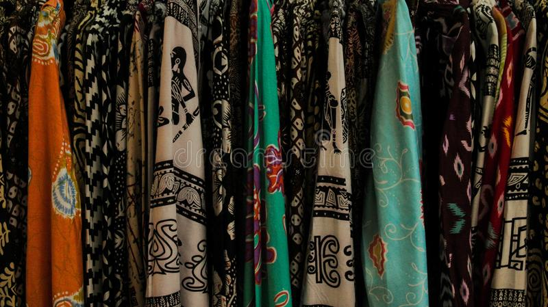 Various kind of woman's batik shirt in a store royalty free stock photography