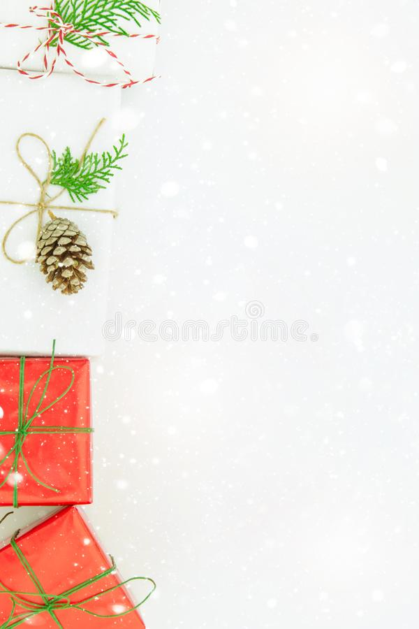 Various kinds of gift boxes wrapped in red white paper tied with twine green ribbon pine cone juniper. Falling snow. Christmas vector illustration